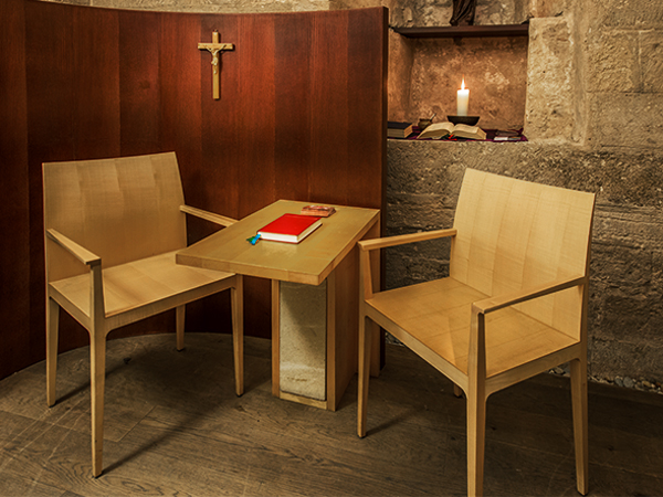 Confessional room with chairs, table, holy cross, candle, and red book
